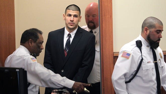 In this Monday, Dec. 23, 2013, file photo, former New England Patriots NFL football player Aaron Hernandez is led into his court appearance at the Fall River Superior Court in Fall River, Massachusetts. Prison officials said Hernandez hanged himself in his cell and was pronounced dead at a hospital early Wednesday.
