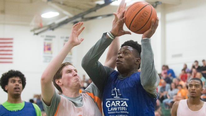 Admiral Schofield attempts to score while defended by Nathan Hastings during the game between Garza Law Firm and DeRoyal Industries in the Pilot Rocky Top League tournament at Knoxville Catholic High School on Monday, June 26, 2017.