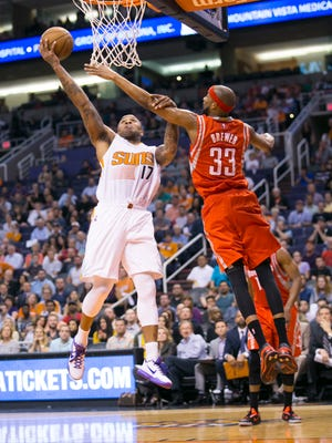 Suns forward P.J. Tucker puts up a shot as the Rockets' Corey Brewer defends during the fourth quarter of the NBA game at  US Airways Center in Phoenix on Feb. 10, 2015.