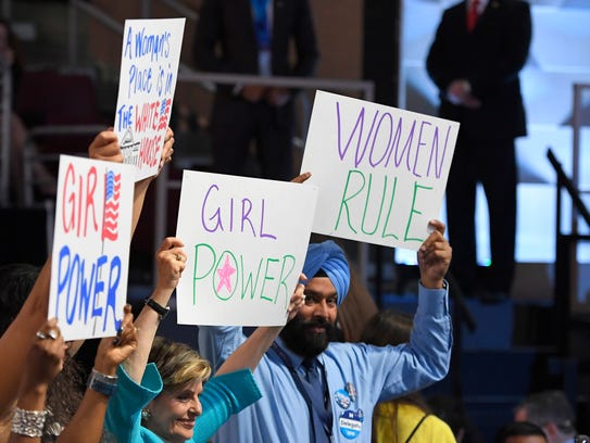 Supporters of Hillary Clinton hold signs during the