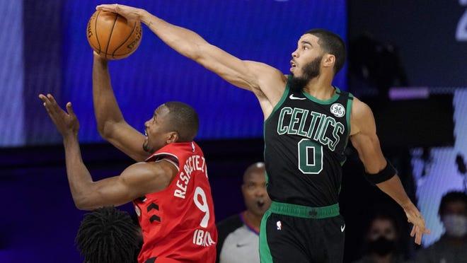 Boston Celtics forward Jayson Tatum (right) blocks the shot of Toronto Raptors' Serge Ibaka during the second half of an NBA conference semifinal playoff basketball game Monday in Lake Buena Vista, Fla.