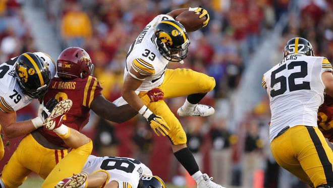 Iowa running back Jordan Canzeri hurdles players as he battles for yards against Iowa State during the Cy-Hawk series on Saturday, Sept. 12, 2015, at Jack Trice Stadium in Ames, Iowa.