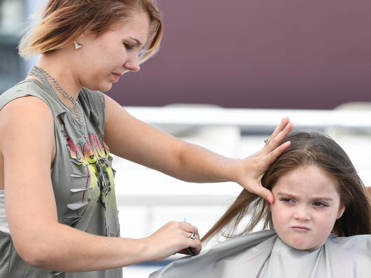 Jacelyn King, 5 years-old, gets her hair cut by Brittany Pierce from the Just Stylin Salon at the Holly House Fun Fair Sunday, September 10, 2017.