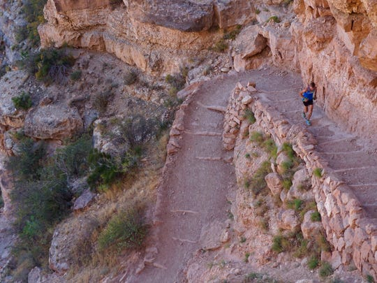 """This Oct. 1 photo provided by HOKA One One shows professional trail runner Tim Freriks running to break the single crossing record (rim-to-rim, or R2R) in the Grand Canyon, Arizona. Freriks blazed from the North Rim to the South Rim at a blistering pace, crossing the 21-mile chasm to claim what is called the """"fastest known time,"""" or FKT. There was no prize, only bragging rights."""