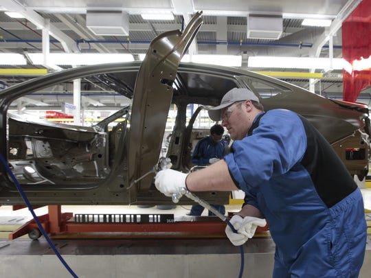 An assembly line worker works on a 2015 Chrysler 200 automobile at the Sterling Heights Assembly Plant in Sterling Heights, Friday, March 14, 2014.