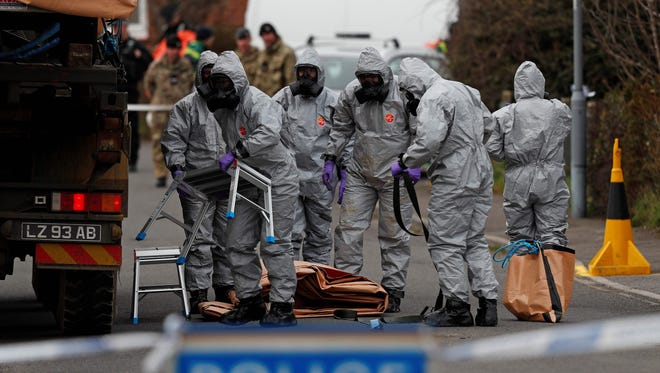 British military personnel wearing protective coveralls work to remove a vehicle connected to the March 4 nerve agent attack in Salisbury, from a residential street in Gillingham, southeast England on March 14, 2018.