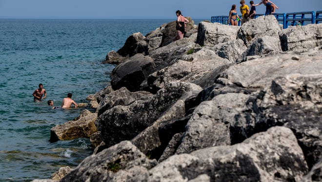 People walk along the break wall and swim Wednesday, June 14, 2017 at Lexington State Harbor.