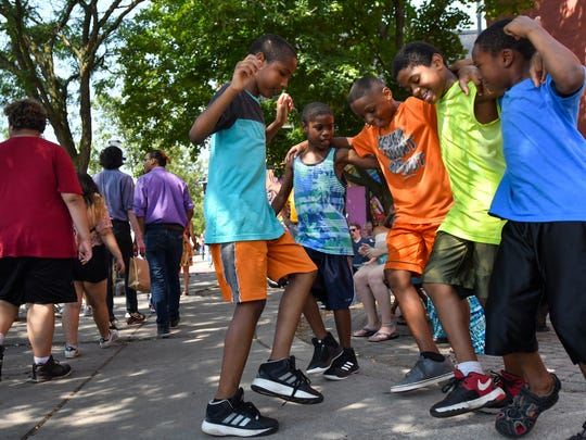From left, cousins Mamir Muhammed, 9, Jeremiah Shakoor, 9, Koamir Muhammed, 11, Ezekial Shakoor, 10, and Patrick Beal, 7, all of Lansing, dance during festivities Aug. 4 at the 24th annual Lansing JazzFest in Old Town.
