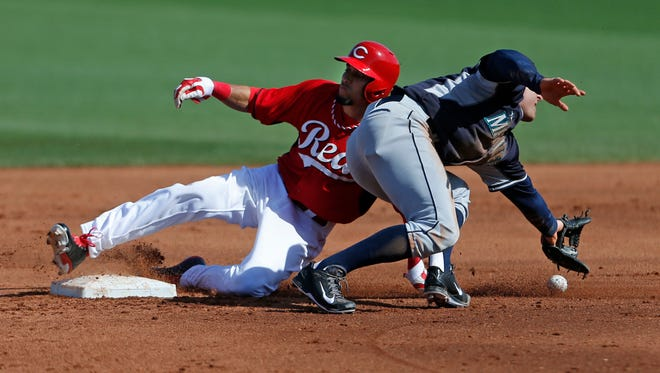 Reds baserunner Billy Hamilton slides safely into second base with a steal as the ball gets away from the Mariners' Brad Miller during a spring training game.