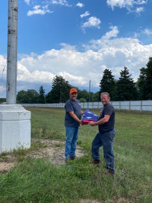 Ionia Free Fair Association Vice President Kirk Wolthuis (left) and Ionia County District 4 Commissioner Candidate Bradley Hawley pose with the American flag Hawley donated to the Ionia Free Fair on Sept. 5.