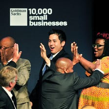 """Sixty-three Detroit and Southeast Michigan small business owners graduating from the Goldman Sachs 10,000 Small Businesses initiative 'high 5' one another as they are brought into the ceremonies. Dignitaries and graduates at the graduation of """"10,000 Small Businesses"""" at the Wayne State University Community Arts Theater in Detroit, Michigan on September 14, 2014."""