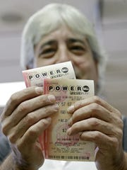 Jose Garrido shows his Powerball tickets Wednesday at a local grocery store in Hialeah, Fla.