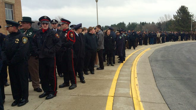 Mourners wait in line outside of Kiel High School for a visitation service for fallen Wisconsin  state trooper Trevor Johnson on Sunday, March 29, 2015.