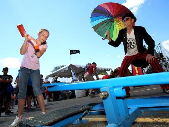 Abigail Curry, 11 of New Hudson, Michigan, takes her turn with a sledge hammer trying to ring the bell as Cap N' Nemo's performer and artist Blake Kuralt, 54 of Chicago, Illinois, watches and encourages her during Maker Faire Detroit at The Henry Ford in Dearborn, Michigan on Saturday, July 29, 2017.