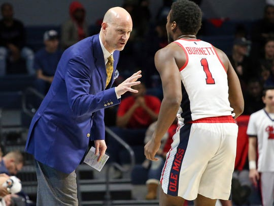 Mississippi coach Andy Kennedy speaks with guard Deandre Burnett (1) during the team's NCAA college basketball game against Arkansas in Oxford, Miss., Tuesday, Feb. 13, 2018. (Petre Thomas/The Oxford Eagle via AP)