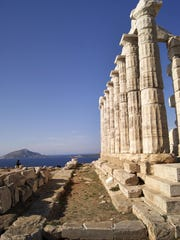 The Temple of Poseidon, an ancient hilltop structure on the southern peninsula of Sounion dedicated to the god of the sea, is seen against a backdrop of the Aegean Sea.