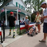 Mason, 10, from the left, his brother Preston, 7, their mother Summer, 37, and father Beau Elston, 37, all of Lacrosse, Wis. walk into the Wright family house, during the Salute to America event.