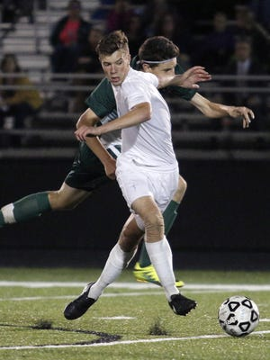Lansing Catholic's Remy Collard controls the ball in front of Williamston's Patrick Schuster Wednesday, Oct. 19, 2016, in Lansing, Mich. Collard scored the Cougars' lone goal in the matchup, and it was voted the LSJ high school video of the week.