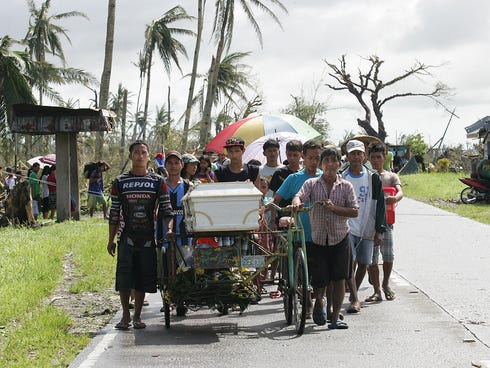Residents wheel a family member to the cemetery on Sunday in Santa Fe, Leyte, Philippines.