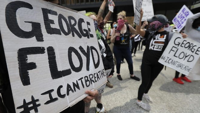 Protesters hold signs before they march during a protest over the death of George Floyd in Chicago on Saturday. Protesters protest in response to George Floyd's death in police custody in Minneapolis on Memorial Day.