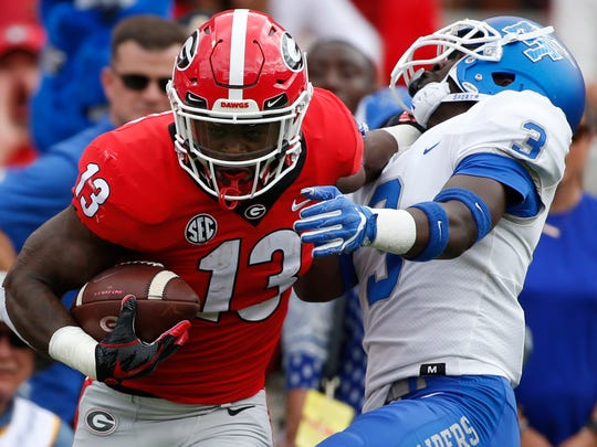Georgia tailback Elijah Holyfield (13) drives past Middle Tennessee safety Gregory Grate Jr (3) during the first half of an NCAA college football game in Athens, Ga., Saturday, Sept. 15, 2018. (Joshua L. Jones/Athens Banner-Herald via AP)