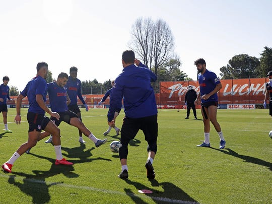 In this photo provided by Atletico Madrid, team players take part in the first group training session on Monday in Madrid, Spain.