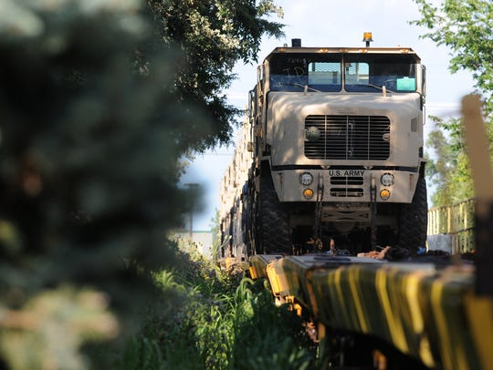 Oshkosh Corp. vehicles sit on a train behind the homes
