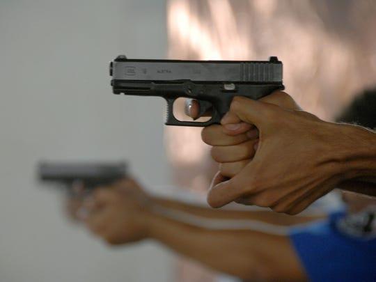 Iraqi policemen aim their glock 9 mm pistols down range