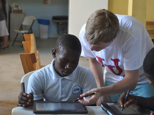 Kyle Leleux, a 2015 St. Thomas More graduate, shows a fifth grade student how to use a tablet computer at Respire Haiti.