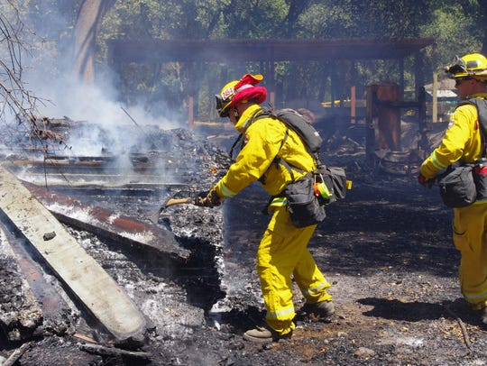 Firefighters pull apart a pile of lumber that burned