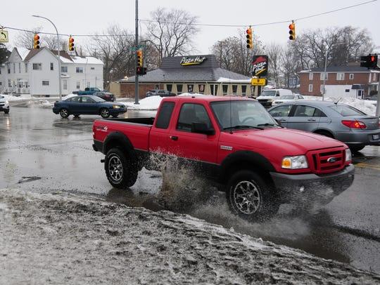 A truck kicks up water after splashing through a pothole