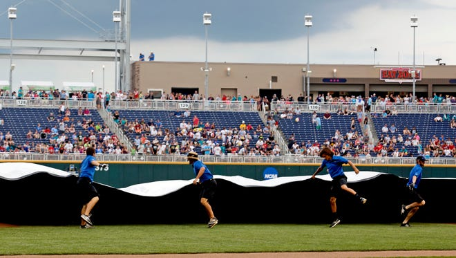 Jun 29, 2016: Grounds crew puts the tarp on the field before the game between the Arizona Wildcats and Coastal Carolina Chanticleers in game three of the College World Series championship series at TD Ameritrade Park.