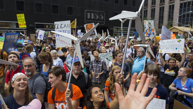 Marchers look up and wave to people above in buildings as they walk  along 6th Ave. during the People's Climate March in New York Sunday, Sept. 21, 2014. (AP Photo/Craig Ruttle)