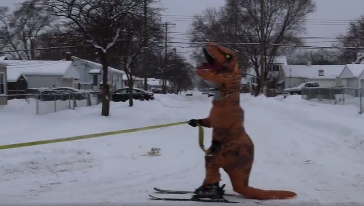 Tyrannosaurus Rex on skis chases Jeep Wrangler down snow-covered Ferndale street