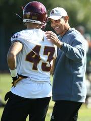Arizona State head coach Herm Edwards talks with safety