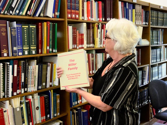 Head librarian Becky Hill holds a copy of Richard Willer's