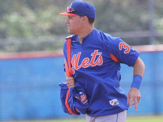 The Mets workout this morning.  Michael Conforto runs out onto the practice field.