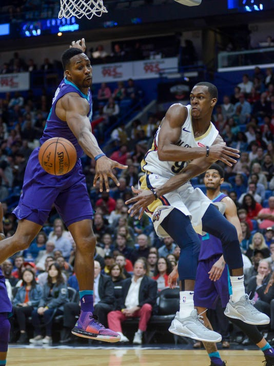 New Orleans Pelicans guard Rajon Rondo, right, passes the ball against Charlotte Hornets center Dwight Howard in the second half of an NBA basketball game in New Orleans on Tuesday, March 13, 2018. New Orleans won 119-115. (AP Photo/Veronica Dominach)