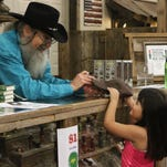 Duck Dynasty cast member Si Robertson chats with 5-year-old Juliette Christian as she hands him a hat to sign during the second annual Faith, Family, Fireworks event at Duck Commander in West Monroe on Friday. Christian and her family traveled from Texas for the event.