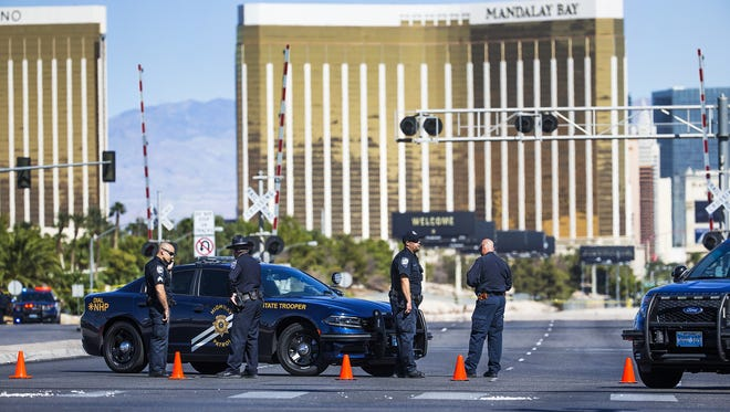 Police stand at a roadblock on Las Vegas Blvd. at Sunset Road with Mandalay Bay in the background Monday morning, October 2, 2017.  At least 58 people were shot to death at a country music concert near Mandalay Bay, Sunday evening, Oct. 1, 2017.