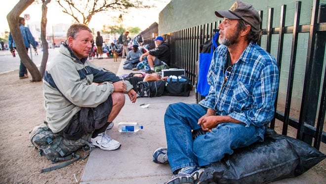 Scott O'Leary (left), a Marine Corps veteran, and David Bagdanov, a U.S. Navy veteran, both homeless, sit across from the overflow shelter at 230 S. 12th Ave. in Phoenix, Wednesday morning at 6 a.m. after the shelter closed for good.