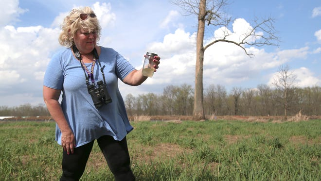 Kathy Wolfe holds a jar of water that she collected from a wetland she owns near the Black Fork River. Wolfe says she was disappointed that she wasn't notified earlier of the spill of bentonite, a chemical used in the drilling process.
