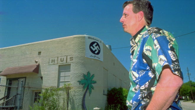 John Houser with a swastika banner he is displaying on his pub in LaGrange, Ga., in 2001.