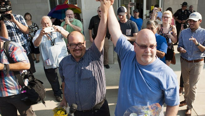 Michael Long (left) and Timothy Long, of Rowan County, raise their hands in front of a crowd of supporters after receiving their legal marriage license at the Rowan County Courthouse September 3, 2015 in Morehead, Kentucky. Kim Davis, an Apostolic Christian and a Rowan County clerk, refused to issue marriage licenses to same sex couples in defiance of a Supreme Court ruling, citing religious objections. Davis was held in contempt of court and placed in Carter County jail on Thursday, September 3rd.