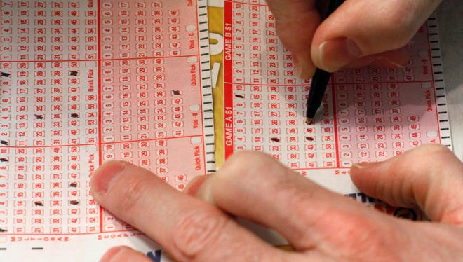 A customer fills out a lottery form for the Mega Millions drawing in Chicago. The Illinois Lottery announced Wednesday that it will be delaying payments to winners of $600 or more until state lawmakers pass a budget.