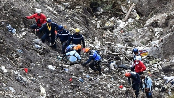 French investigators work through scattered debris on March 26, 2015, at the crash site of the Germanwings Airbus A320 in the French Alps above the southeastern town of Seyne.