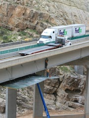 Traffic passes over a bridge while construction crews work beneath them in the Virgin River Gorge.