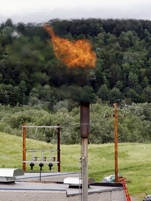 Methane gas burns off a stack near the Washington Electric Cooperative power plant in Coventry, Vt.