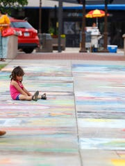 People stop to look at ChalkFest artwork in The 400 Block in July 2016, in downtown Wausau.