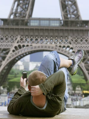 An unidientified man uses a cellular phone next to the Eiffel Tower in Paris.
